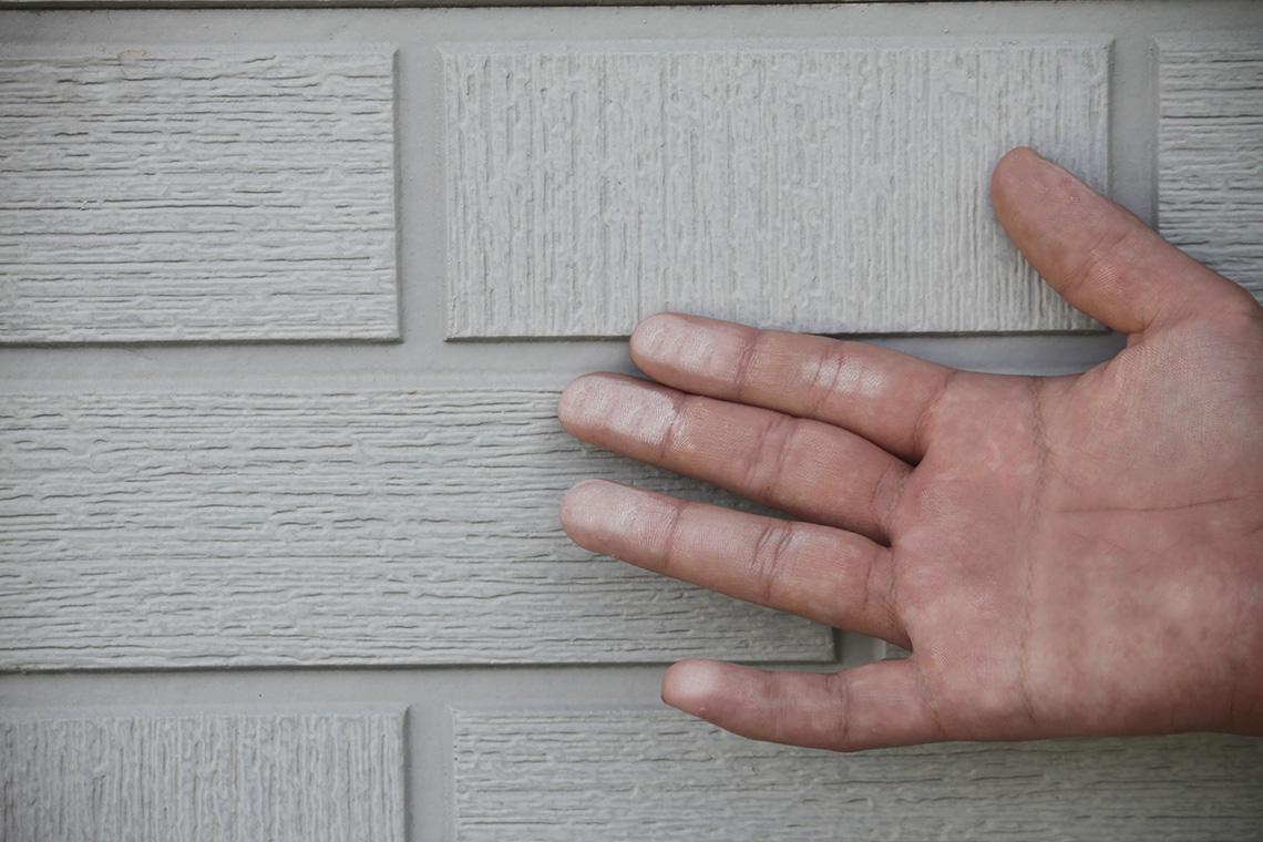 外壁に触って白い粉がついた手